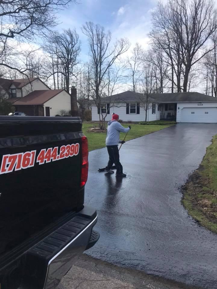 man sealcoating residential driveway